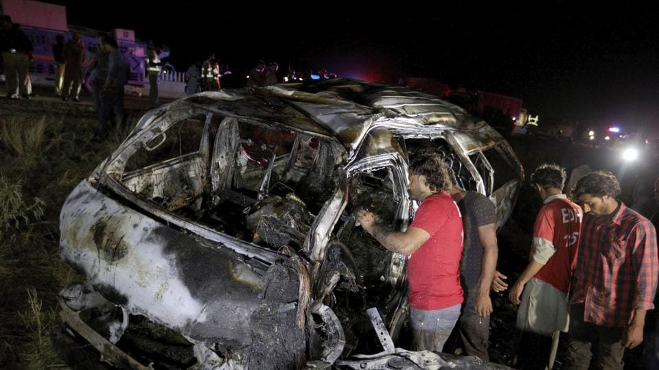 Rescue workers examine a burnt bus at the accident site on a highway outside of Karachi, Pakistan.
