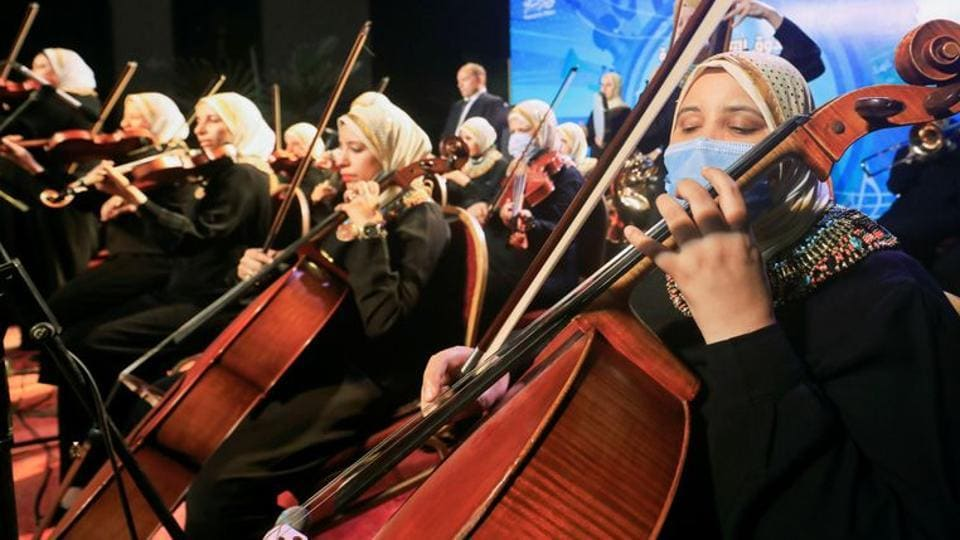 A member of Al-Nour Wal Amal (Light and Hope) chamber orchestra wears a protective mask as she plays during the first concert.