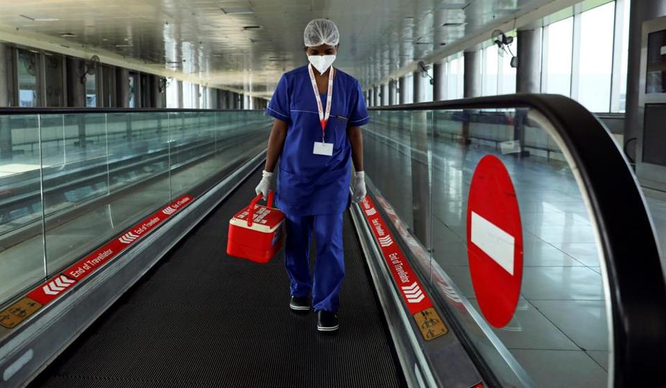 A laboratory technician carries swab samples collected from passengers amidst the spread of the coronavirus disease (Covid-19) at Indira Gandhi International Airport, in New Delhi, India, September 12, 2020.