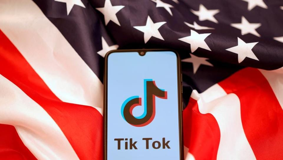 TikTok's logo is displayed on the smartphone while standing on the US flag.