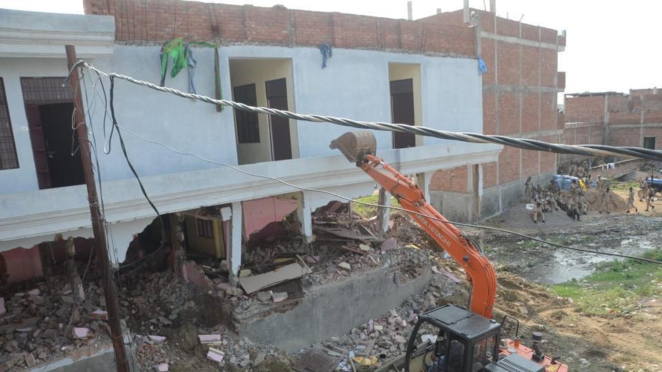 An excavator demolishing an illegal construction in Beli in Prayagraj on  Sunday.