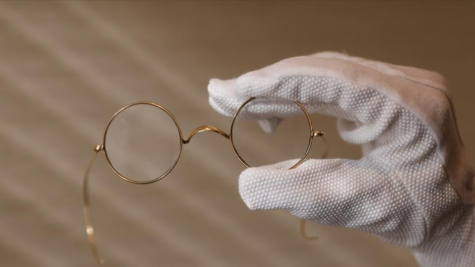 A member of staff holds a pair of round Windsor spectacles that belonged to John Lennon at Sotheby's auction house ahead of their