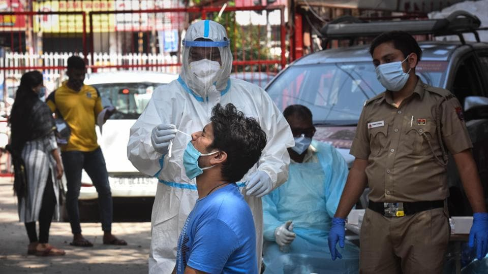 A health worker in PPE coveralls collects a swab samples for coronavirus testing, at Hudson Lane, in New Delhi on Sunday