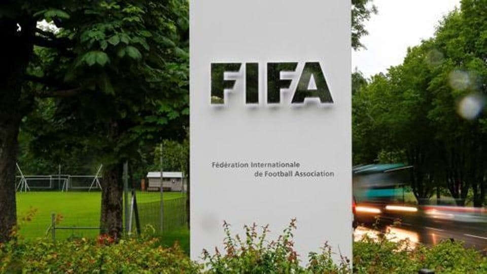 Cars drive past a logo in front of FIFA's headquarters in Zurich.