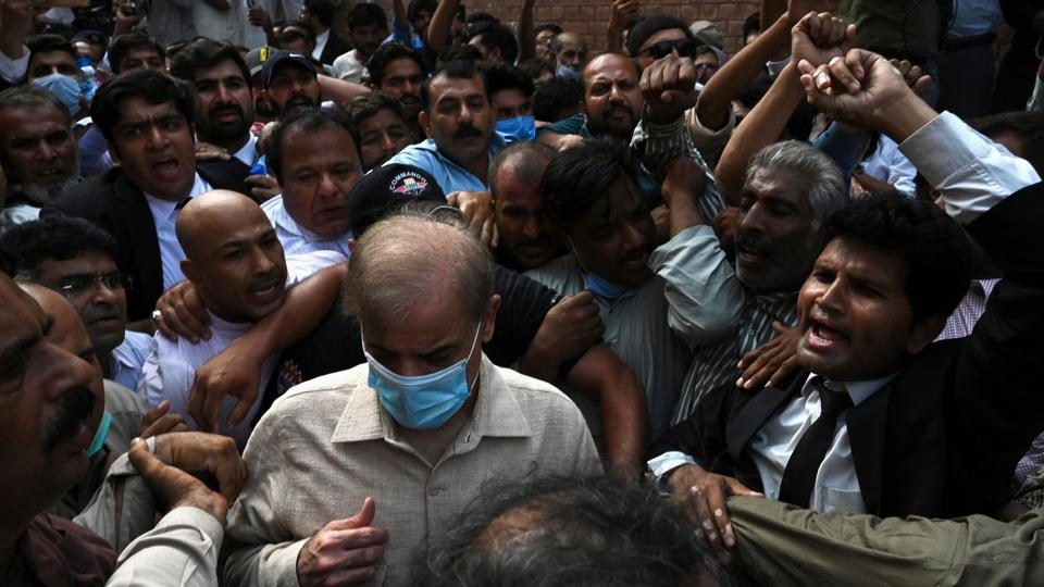 Shahbaz Sharif (Centre wearing blue mask), Pakistani opposition leader and brother of former prime minister Nawaz Sharif, comes out from the Lahore high court surrounded by supporters after the court rejected his bail plea in a money laundering and assets beyond income case.
