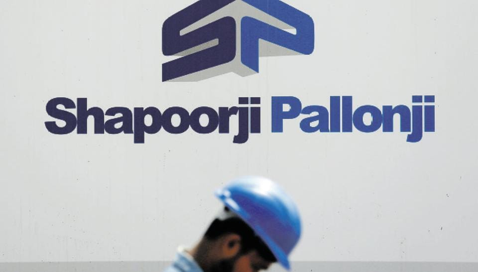 A construction worker walks past a hoarding of Indian conglomerate Shapoorji Pallonji Group on the outskirts of Mumbai.
