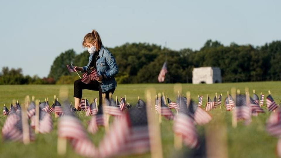 A volunteer places American flags representing some of the 200,000 lives lost in the United States in the coronavirus disease (Covid-19) pandemic on the National Mall in Washington.