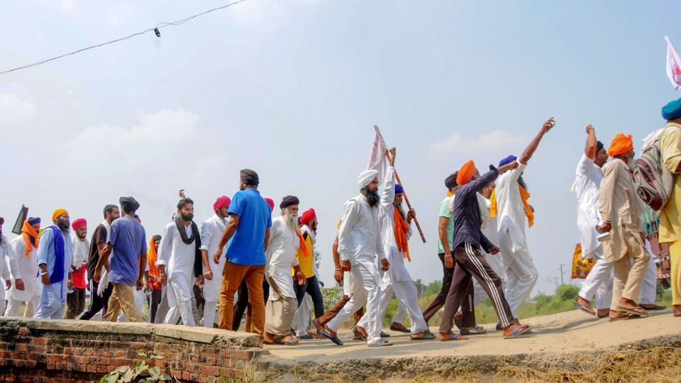 Protestors raise slogans as they arrive to join farmers in their ongoing 'Rail Roko' at Devi Dass Pura village, Punjab.