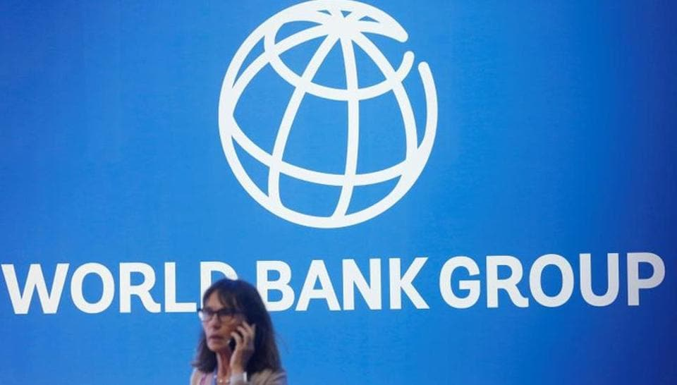 A woman standing near a logo of World Bank  (REUTERS/Johannes P. Christo/File Photo)