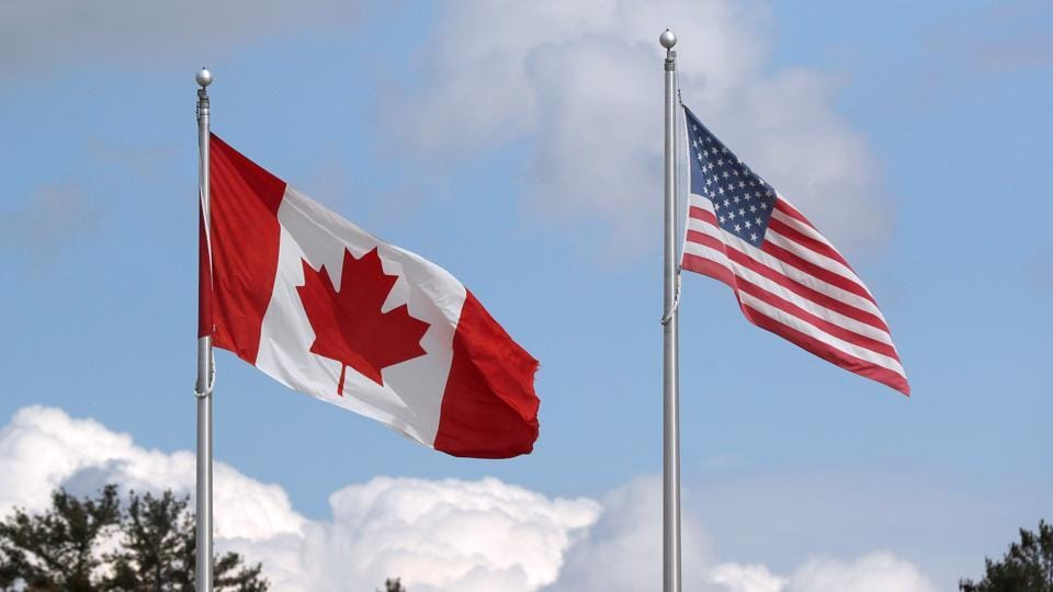 A US and a Canadian flag flutter at the Canada-United States border crossing at the Thousand Islands Bridge, which remains closed to non-essential traffic to combat the spread of the coronavirus disease (Covid-19) in Lansdowne, Ontario.