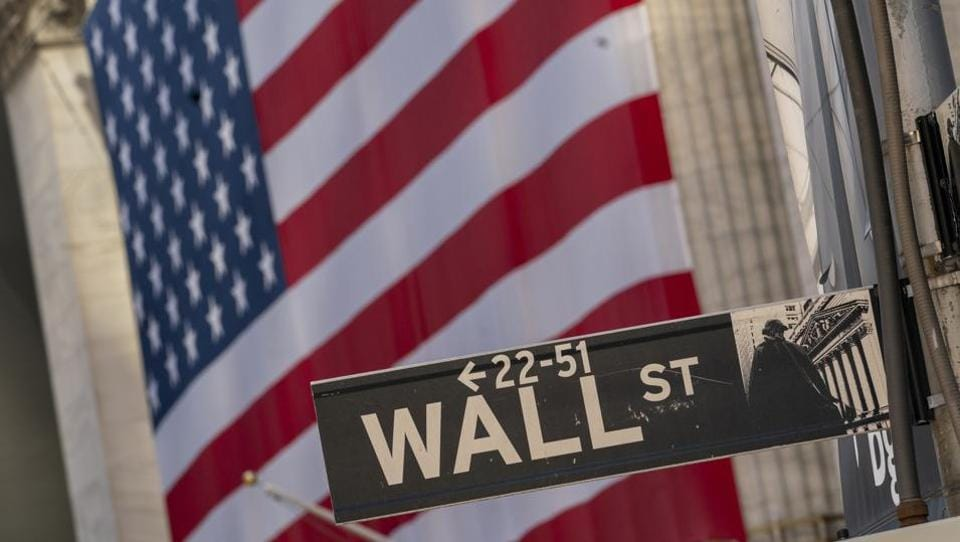 The Wall Street sign is framed by a giant American flag hanging on the New York Stock Exchange.