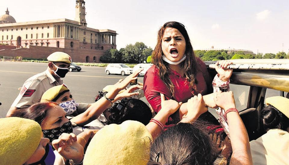 A Congress party worker shouts slogans while being detained during a flash protest against Hathras gang-rape at Vijay Chowk, near Parliament House in New Delhi on Tuesday.