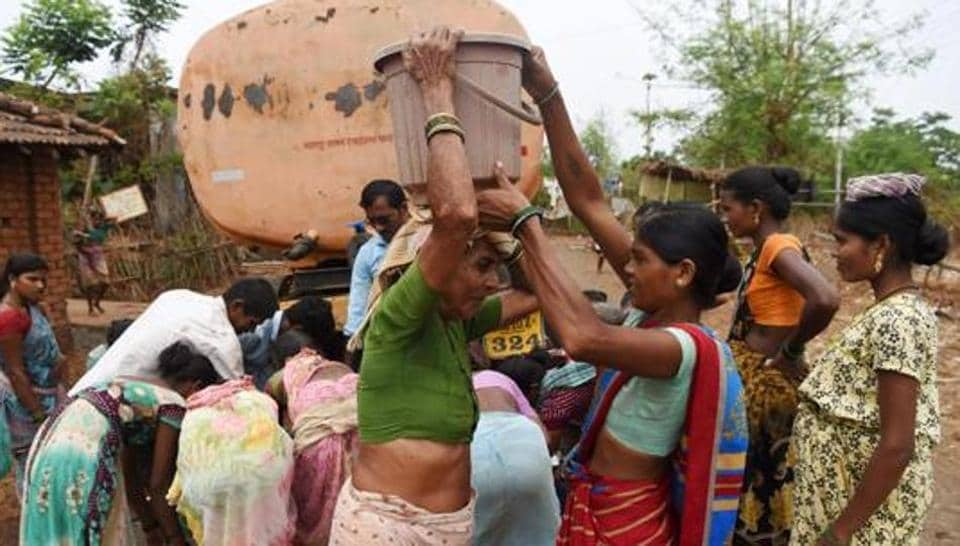 A woman assists an elderly to carry a bucket filled with tanker water at Shakar Pada village near Shahapur, on the outskirts of Mumbai.