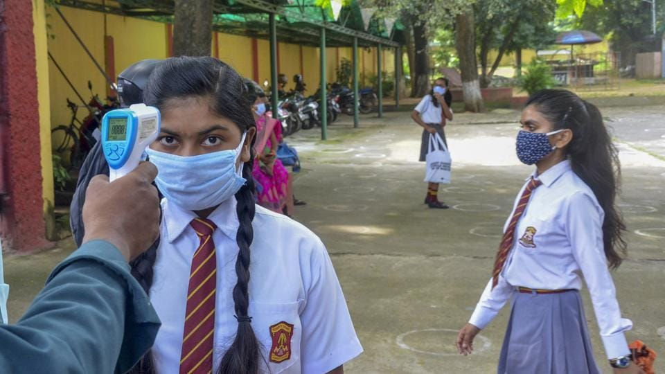 A student undergoes thermal screening before she entersthe school to submit her personal assessmentproject for the upcoming annual examination, during Unlock 4, in Ranchi.