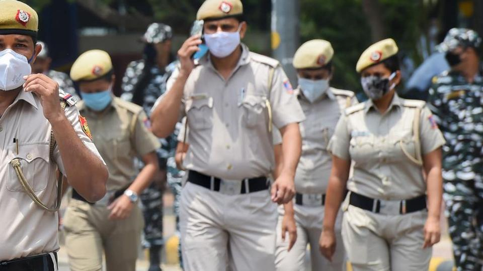 Police personnel wearing protective masks patrol a street in New Delhi.