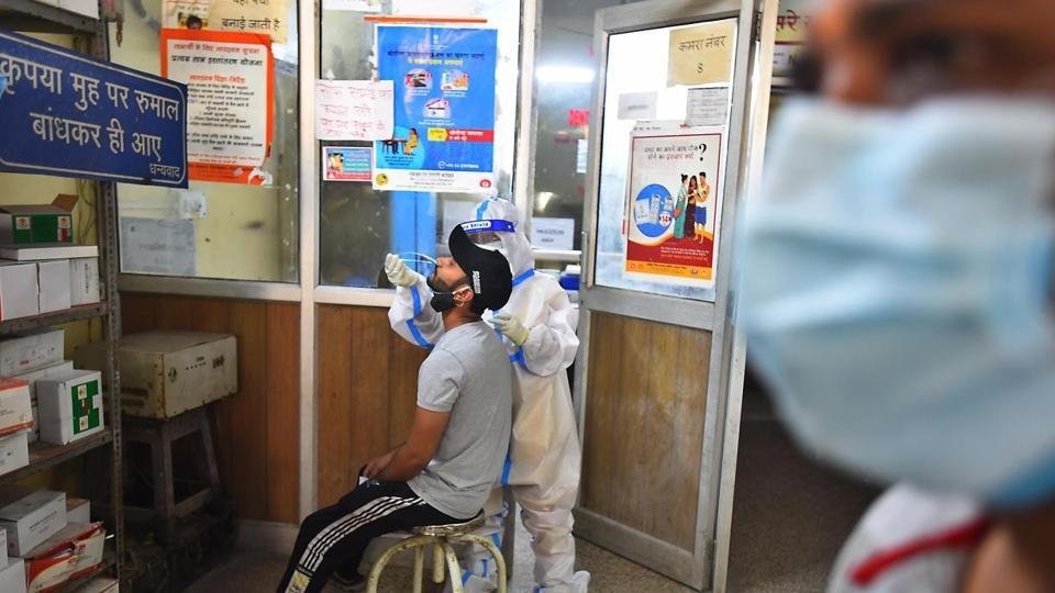 A health worker in PPE coveralls collects a swab sample from a person for coronavirus testing, at a government dispensary in New Delhi.