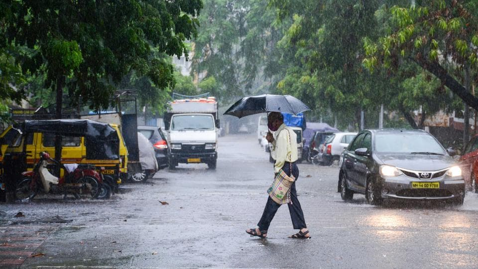 A man shields himself under umberlla at it rained in Kothrud in Pune.