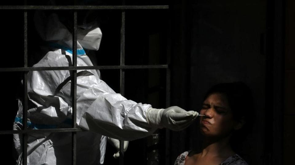 A healthcare worker wearing personal protective equipment (PPE) collects a swab sample from a woman, amid the spread of the coronavirus disease (COVID-19), in New Delhi.