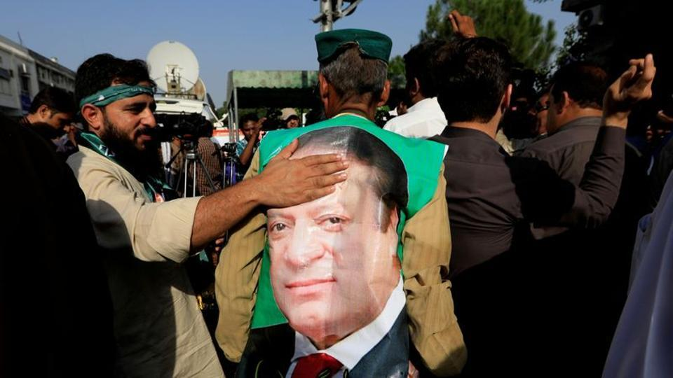 A supporter of former Pakistani prime minister Nawaz Sharif touches his picture during a  demonstration.