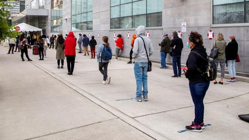People wait in line at the Women's College Covid-19 testing facility in Toronto, Ontario, Canada.