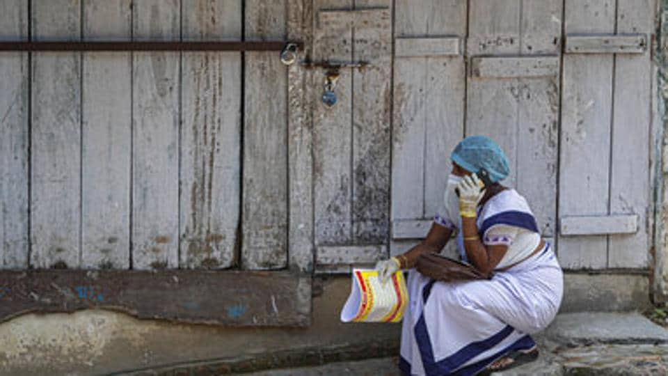 An Indian health worker talks on her mobile phone while waiting for a Covid-19 positive patient in Guwahati.