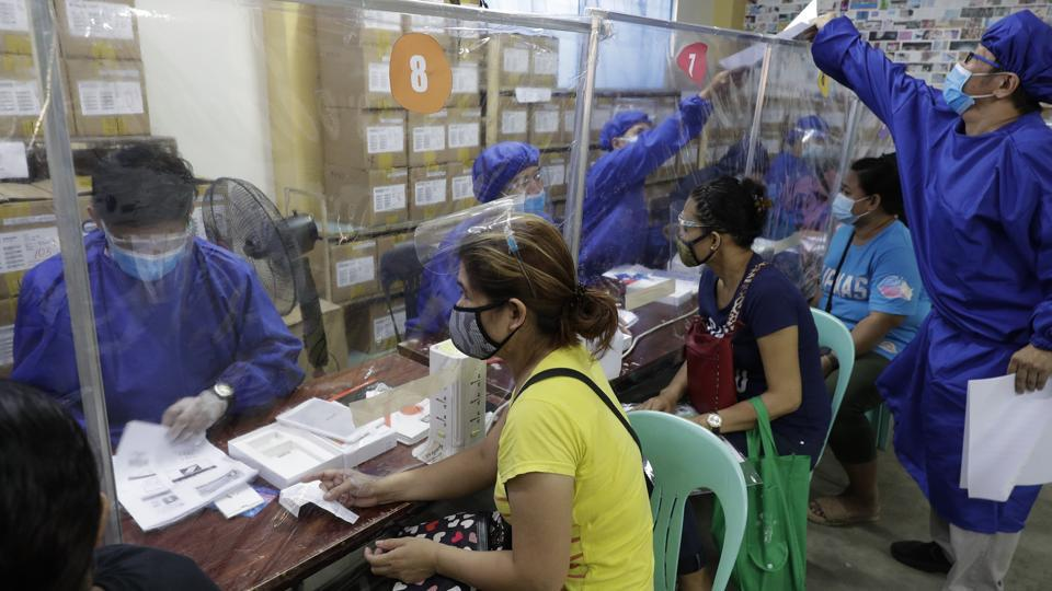 Teachers wearing protective suits to prevent the spread of the coronavirus, distribute student electronic tablets as they prepare for online classes at the opening of school next week at the Dona Rosario High School in Quezon city, Philippines, Thursday, Oct. 1, 2020.