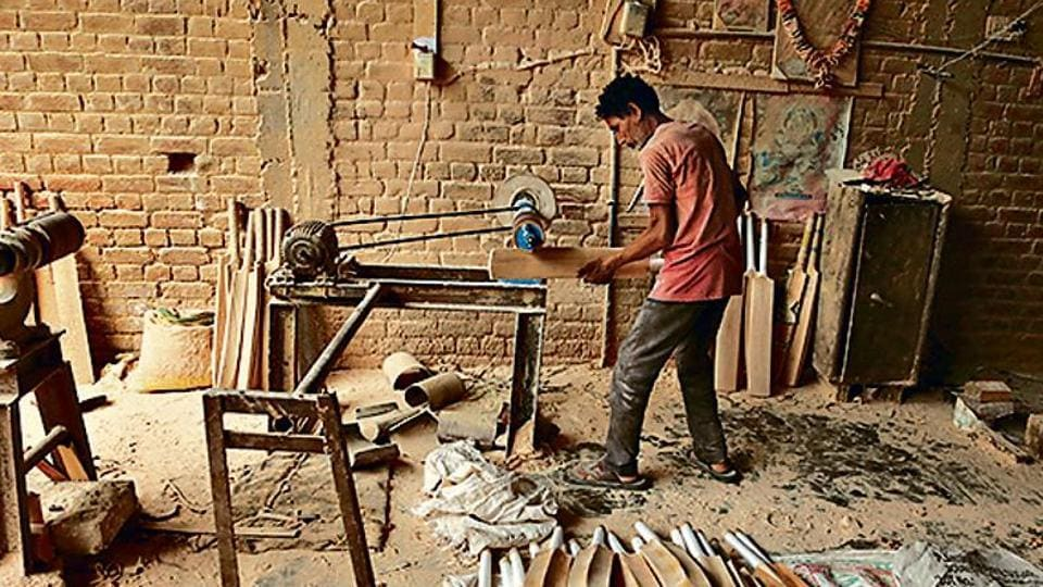 A worker gives finishing touches to a cricket bat at a factory on the outskirts of Jammu.