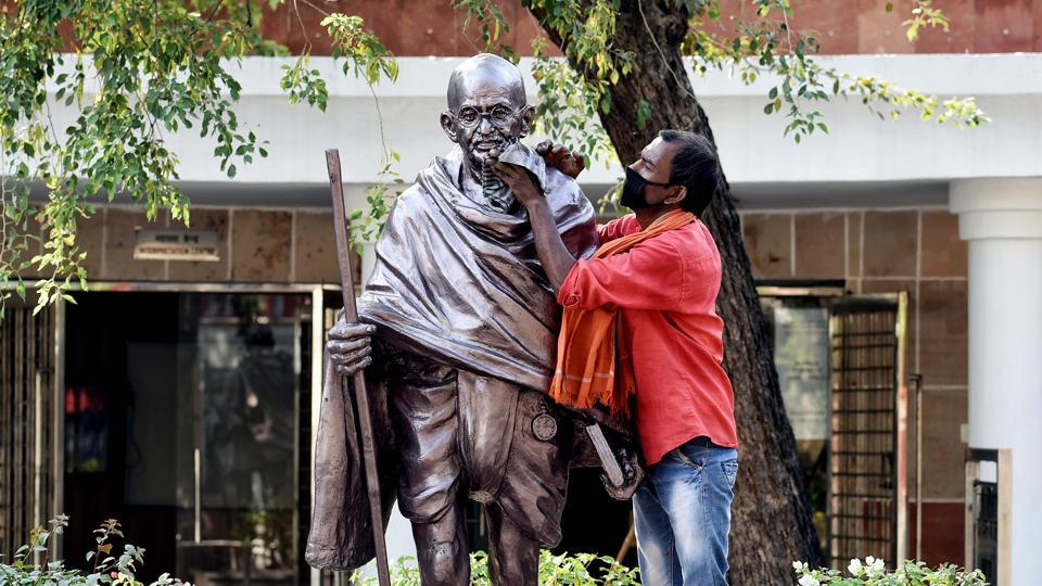 A worker cleans the statue of Mahatma Gandhi on the eve of Gandhi Jayanti at Rajghat in New Delhi on Thursday.