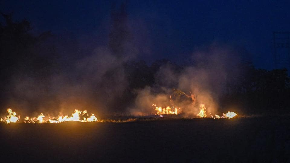 Smoke rises from straw stubble being burnt in a field at night after the paddy crop harvest, in Karnal, Haryana.
