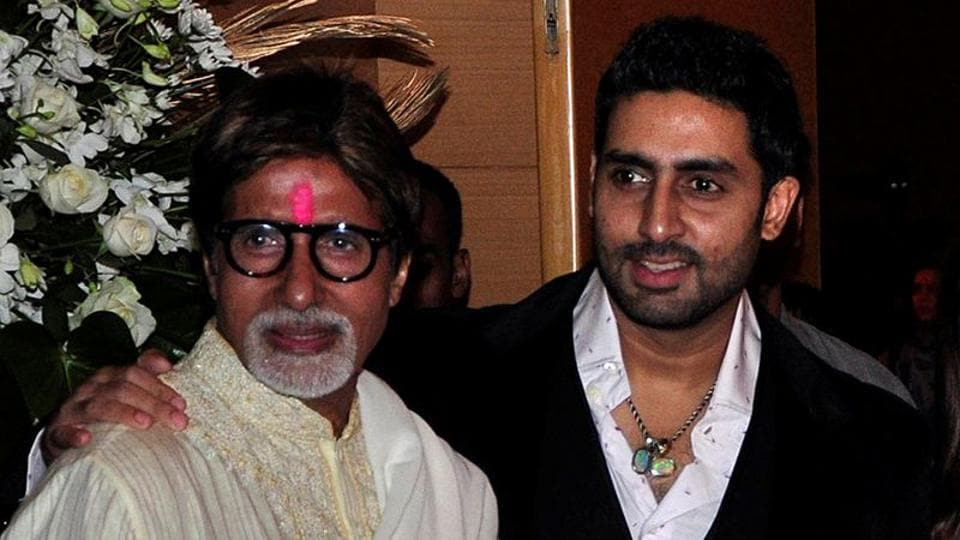 Bollywood actors Amitabh Bachchan (L) and his son Abhishek Bachchan pose for a picture during a party.