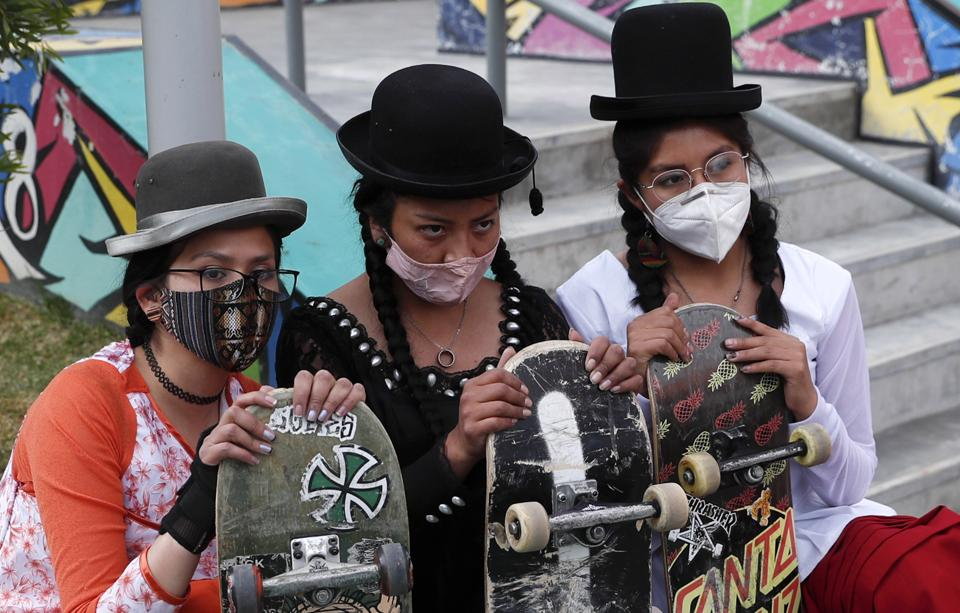 Yanira Villarreal, left, Ayde Choque, center, and Milenda Limachi, wearings masks amid the COVID-19 pandemic and dressed as a