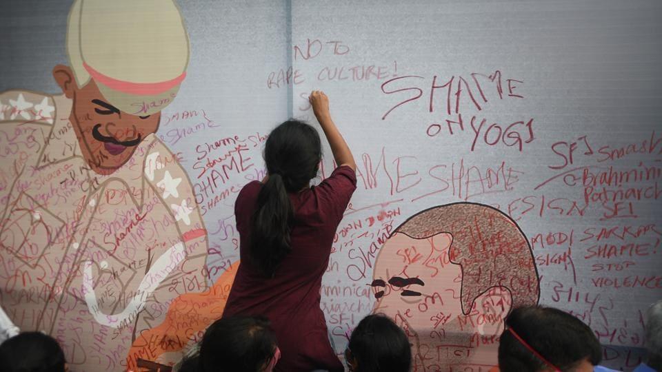 A woman makes a mural as a mark of protest demanding justice for Hathras gang-rape victim, at Jantar Mantar, in New Delhi.