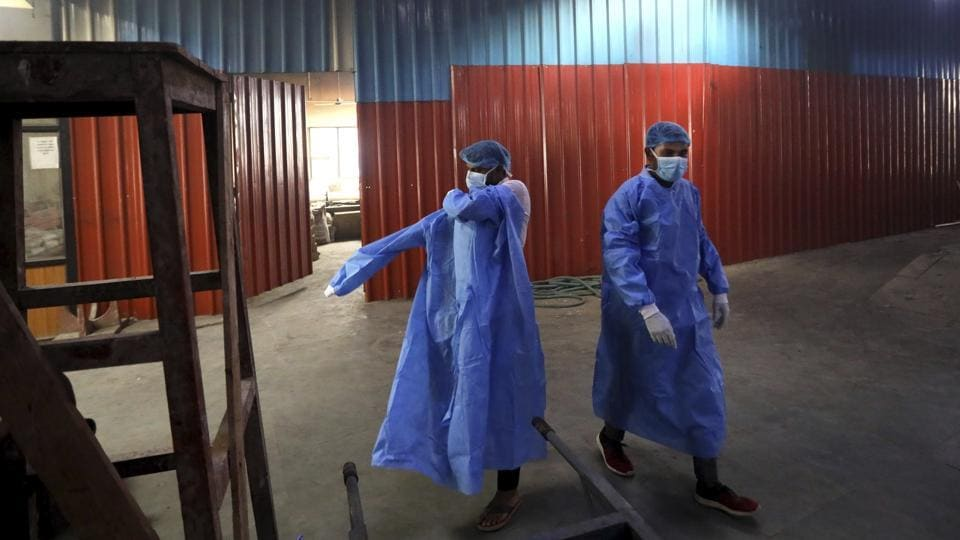 Workers put on personal protective suits before carrying the body of a Covid-19 victim for cremation in New Delhi.