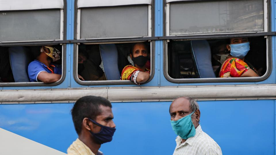 Commuters wearing face masks to prevent coronavirus wait inside a bus as pedestrians walk past at a bus terminus in Kolkata, India, Thursday, Oct. 1, 2020. India is expected to become the pandemic's worst-hit country within weeks, surpassing the United States. (AP Photo/Bikas Das)