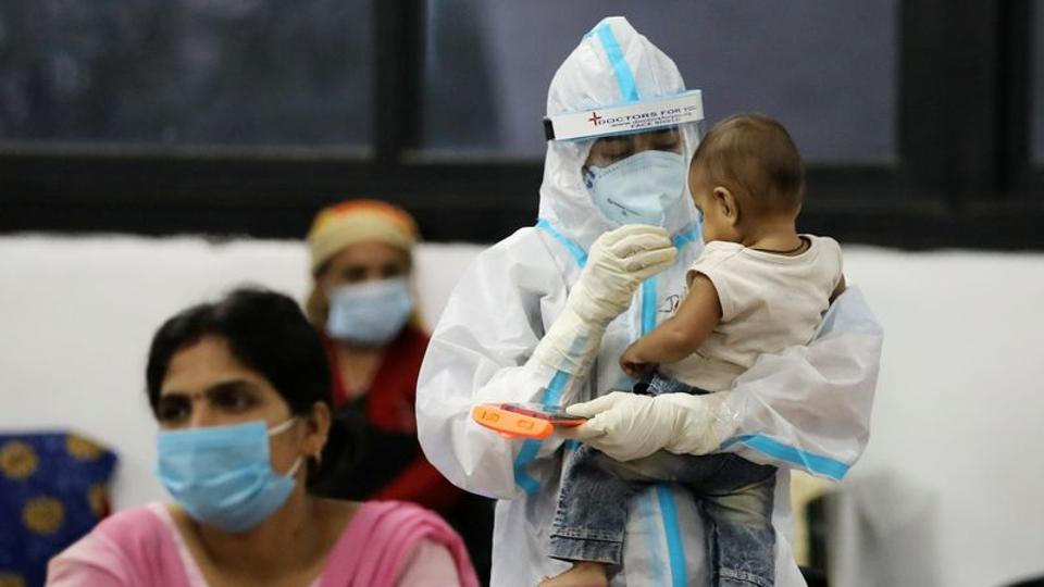 A medical worker in PPE plays with a child of woman recovering inside a quarantine centre in New Delhi.