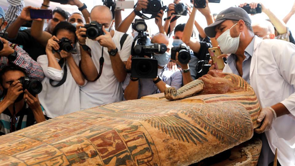 A sarcophagus is opened in front of a swarm of media persons at a newly discovered burial site near Egypt's Saqqara necropolis, in Giza on October 3. Archaeologists in Egypt said on October 3 that they had found 59 well-preserved and sealed wooden coffins, with mummies inside most of them,  over recent weeks that were buried more than 2,500 years ago. (Mohamed Abd El Ghany / REUTERS)