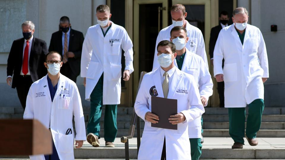 Dr Sean Conley, White House physician (C) arrives with a team of doctors for a press conference outside Walter Reed National Military Medical Center in Bethesda, Maryland on October 4. The last-minute limousine outing came with Trump's doctors satisfied enough about his progress to suggest the possibility of his being discharged on October 5, AFP reported. (Michael Reynolds / Bloomberg)