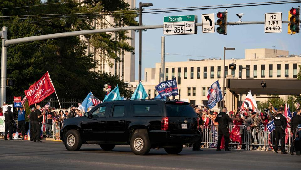 A vehicle in US President Trump's motorcade drives past supporters as they rally outside Walter Reed Medical Center in Bethesda, Maryland on October 4. Experts criticised the move saying that the outing broke his own government's public health guidelines requiring patients to isolate while they are in treatment and still shedding virus--and endangered his Secret Service protection.  (Alex Edelman / AFP)