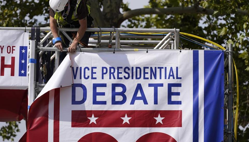 A worker hangs a banner as preparations take place for the vice presidential debate outside Kingsbury Hall at the University of Utah, Monday.