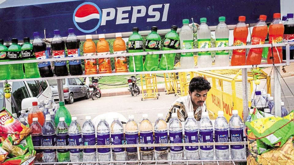 A street vendor is seen behind PepsiCo. products displayed for sale on a cart in New Delhi.