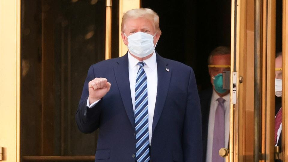 US President Donald Trump makes a fist as he walks out the front doors of Walter Reed National Military Medical Center after a fourth day of treatment for the coronavirus disease (Covid-19) while returning to the White House in Washington from the hospital.
