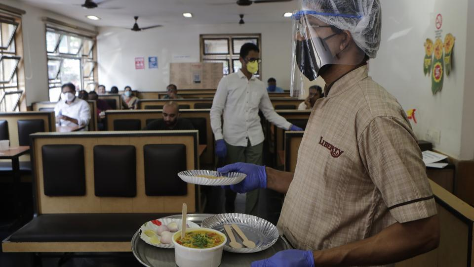 A server wears a face-shield while carrying orders at Liberty Hotel in Mumbai on October 5. Hotels, food courts, restaurants and bars in Maharashtra resumed services on October 5, after a gap of nearly six months in the wake of coronavirus pandemic. (Anshuman Poyrekar / HT Photo)