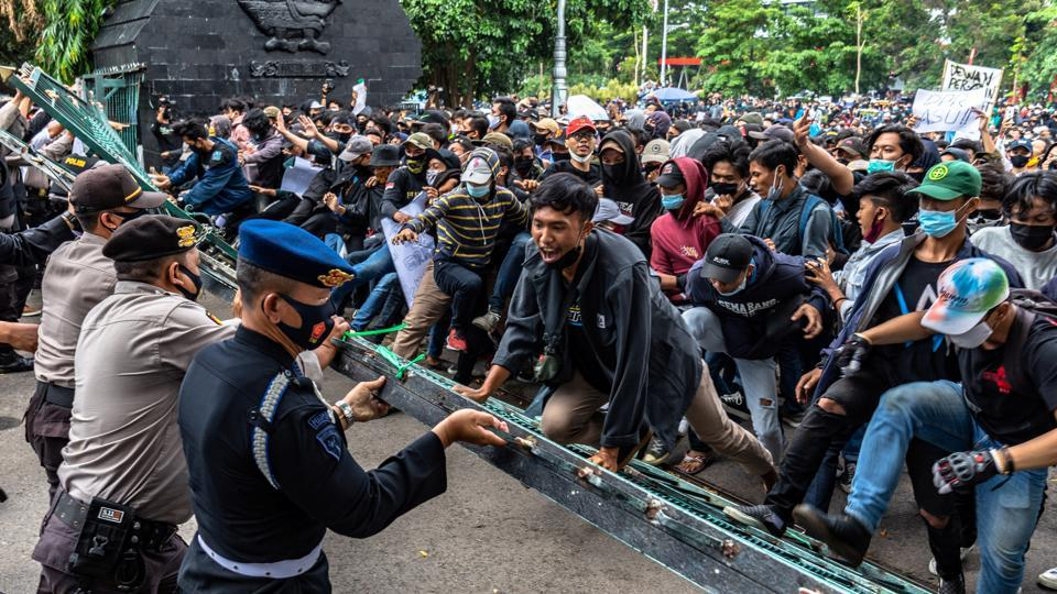 Demonstrators and police officers face off during a protest against the government's labour reforms outside Regional People's Representative Assembly building in Semarang on October 7.  The new law is intended to improve bureaucratic efficiency and cut red tape as part of efforts by President Joko Widodo's administration to attract more investment in the vast archipelago nation, home to more than 270 million people. (Aji Styawan / Antara Foto via REUTERS)