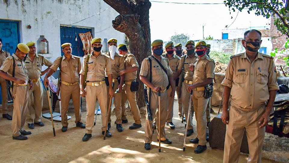 Police personnel stand guard outside the residence of a 19-year-old Dalit woman who died after being allegedly gang-raped, at Bulgadi village in Hathras.