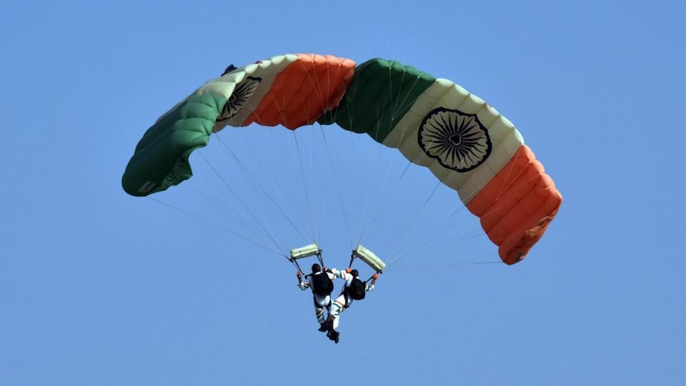 """Indian Air Force (IAF) paratroopers perform during the 88th Indian Air Force Day celebrations at Hindon Airbase in Ghaziabad on October 8. The IAF was established on October 8, 1932, in undivided India under colonial rule. It was given the prefix """"Royal"""" by King George VI for its contribution during the Second World War. The prefix was later dropped in 1950 when India became a republic. (Sanjeev Verma / HT Photo)"""