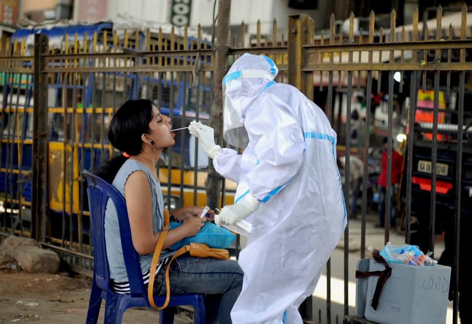 A health worker wearing a PPE kit collects a sample from a woman for the COVID-19 Rapid Antigen Test, at a city market in Bengaluru.