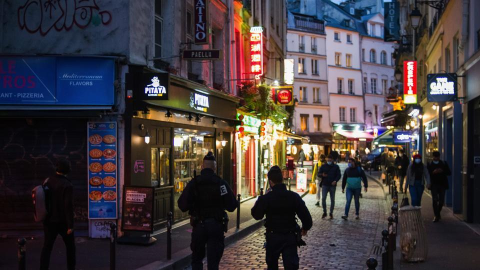 Police patrol near illuminated take away food outlets as new coronavirus measures come into force for bars and restaurants, at night in Paris, France on October 6, 2020.