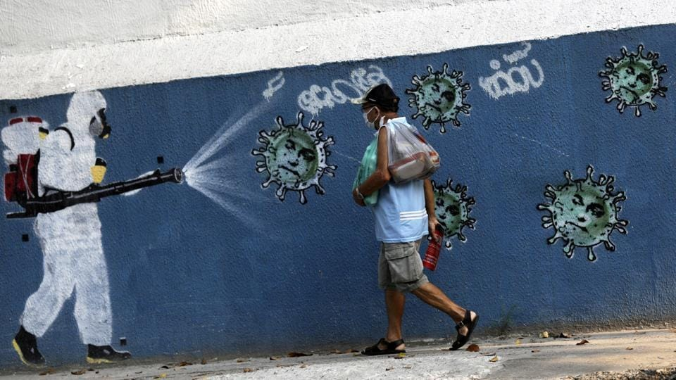A man walks next to a graffiti depicting a cleaner in protective gear spraying viruses with the face of Brazil's President Jair Bolsonaro in Rio de Janeiro on October 7. According to John Hopkins University's tally, Brazil surpassed 5 million confirmed coronavirus cases on October 7 to become world's third hardest coronavirus-hit country.  (Ricardo Moraes / Reuters)
