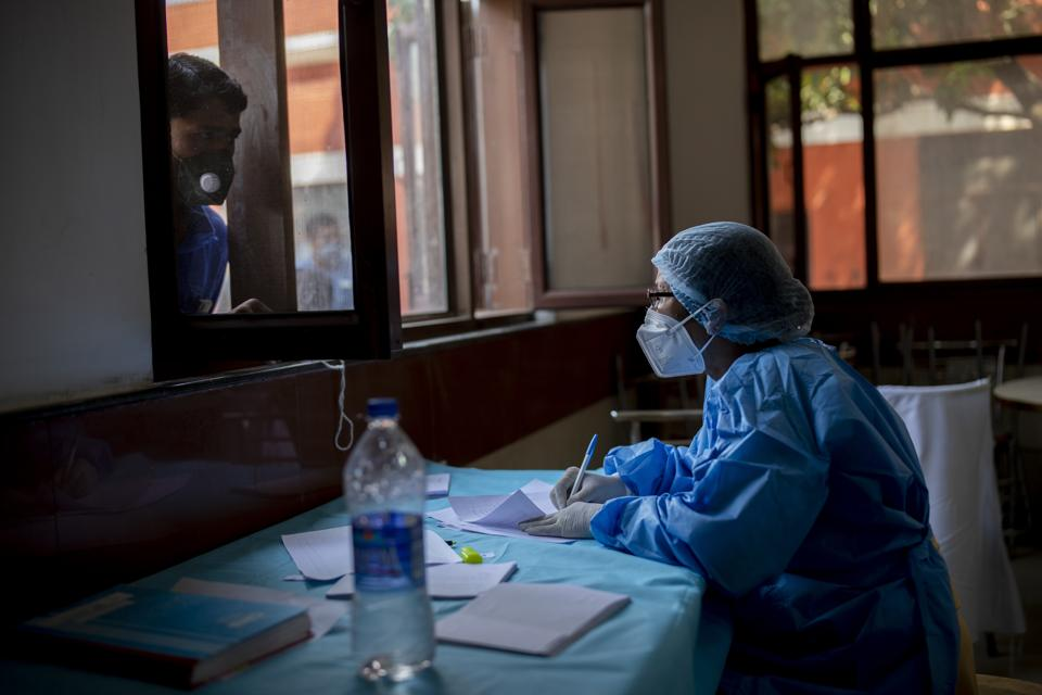 A health worker notes down the name of a person before he is tested for Covid-19 in New Delhi on October 8, 2020.