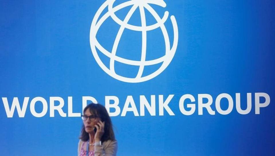 A participant stands near a logo of World Bank at the International Monetary Fund - World Bank Annual Meeting 2018 in Nusa Dua, Bali, Indonesia.